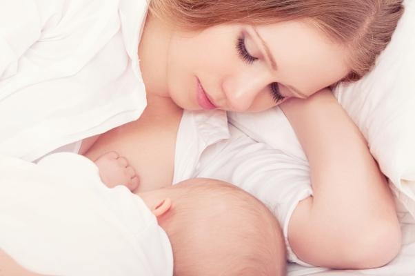Малыш в белой пелёнке лёжа сосёт грудь мамы в белой рубашке