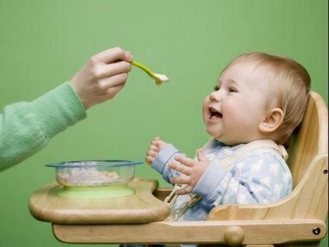 Ребёнка в голубой кофточке кормят с ложечки, он смеётся