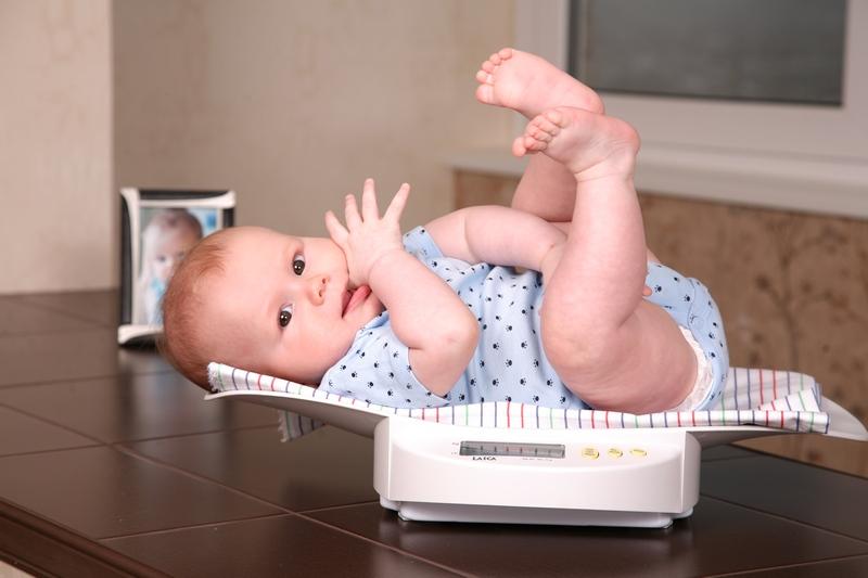 Ребёнок в голубом боди сосёт палец, лежит на весах