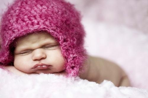Спящий насупленный малыш в розовой вязанной шапке