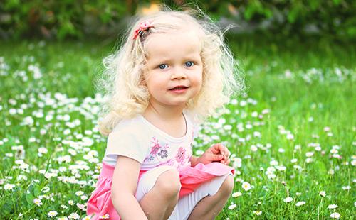 Светловолосая девочка на поле цветов